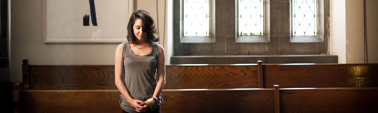 A young lady praying while standing in the pews of a church.