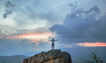 Man on mountain praising God