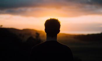 Man looking into sunrise horizon