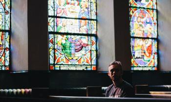 Young man sitting in pew