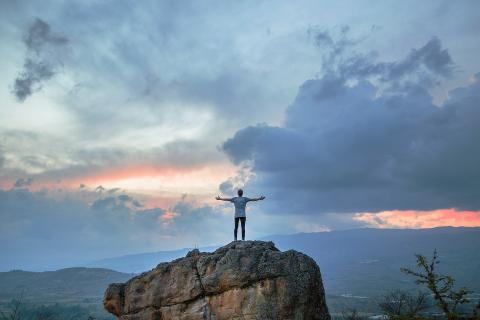 Man on mountain praising God