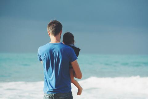 Dad and child by the ocean surf